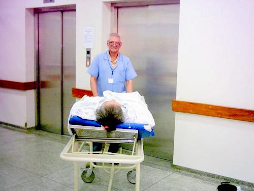 Sr. Antonio, voluntário no HGT, transportando paciente para clínica médica.